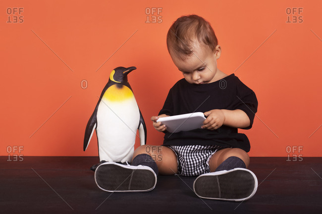 Baby girl ignoring toy while using mobile phone sitting against orange background