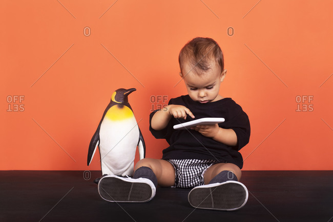 Baby girl using smart phone while sitting by toy against orange background