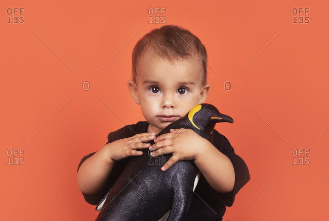 Cute baby girl hugging penguin toy while sitting against orange background