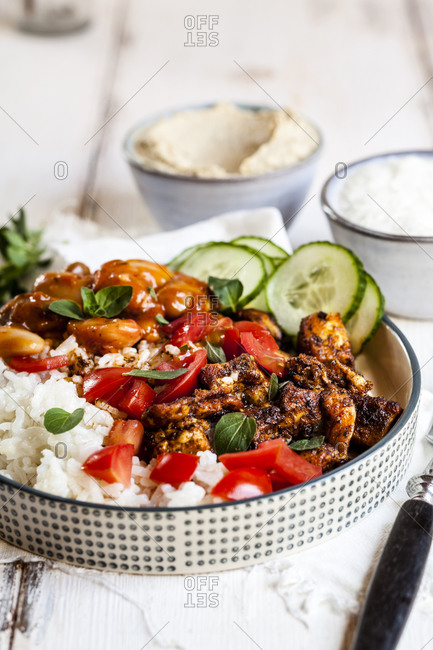Bowl of Greek gyro with rice- fava beans- halloumi cheese- tomatoes and cucumbers