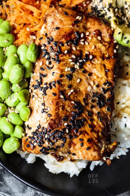 Bowl of teriyaki salmon with rice- carrot salad- edamame beans- avocado and sesame seeds