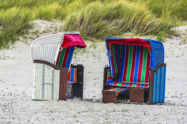 Old fashioned hooded beach chairs on beach