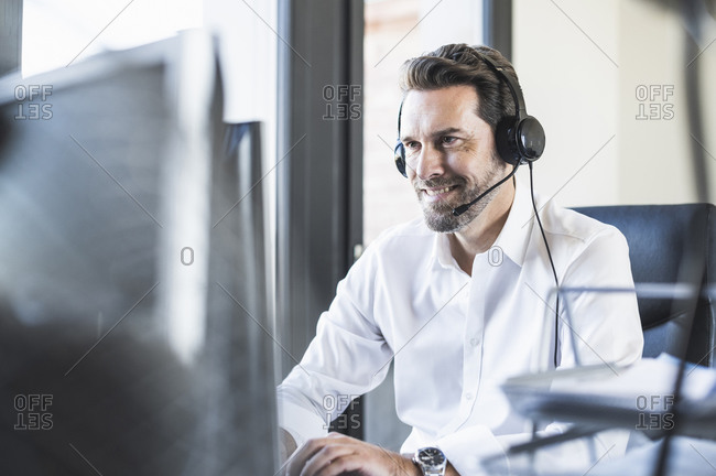 Businessman wearing headphones using computer while sitting at office