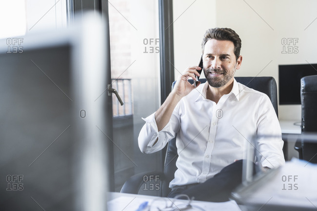 Mature businessman talking on mobile phone while sitting on chair at office
