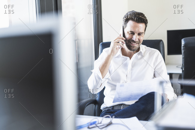 Businessman looking at paper while talking on mobile phone sitting at office