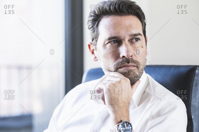 Businessman with hand on chin looking away while sitting at office
