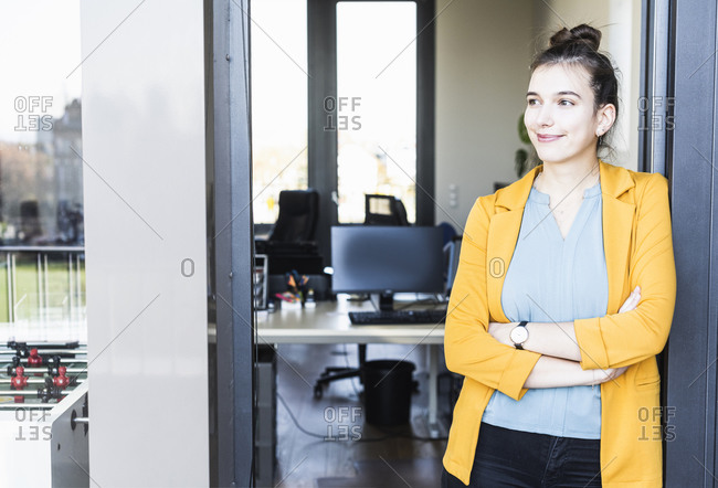 Smiling businesswoman standing with arms crossed at office entrance
