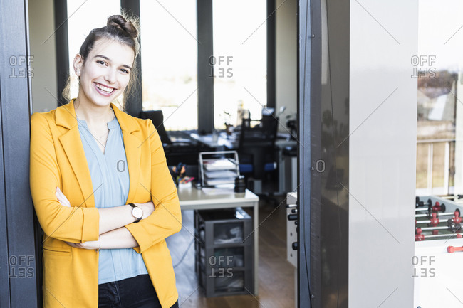 Young businesswoman smiling while standing at entrance in office