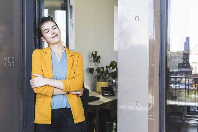 Young businesswoman with arms crossed and eyes closed standing by door at office