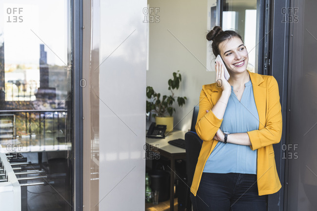 Businesswoman talking on mobile phone while standing at door in office