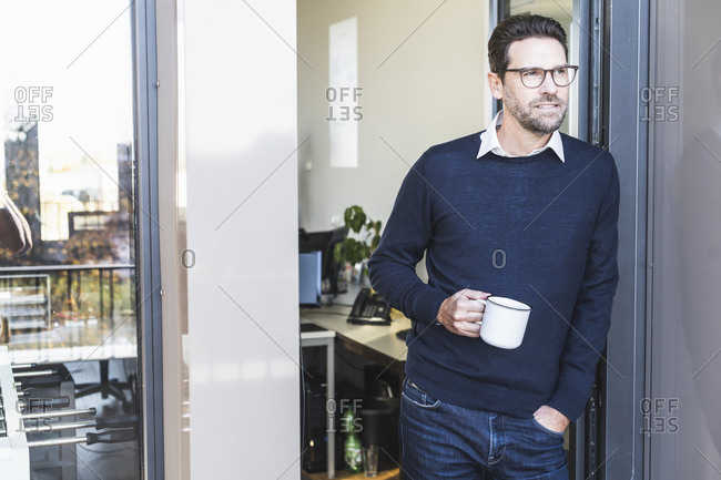 Businessman with coffee cup standing at office entrance
