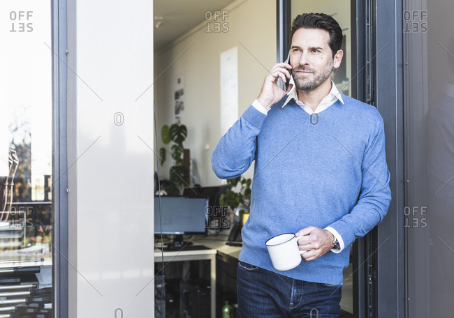 Mature businessman with coffee cup talking on mobile phone while standing at office entrance