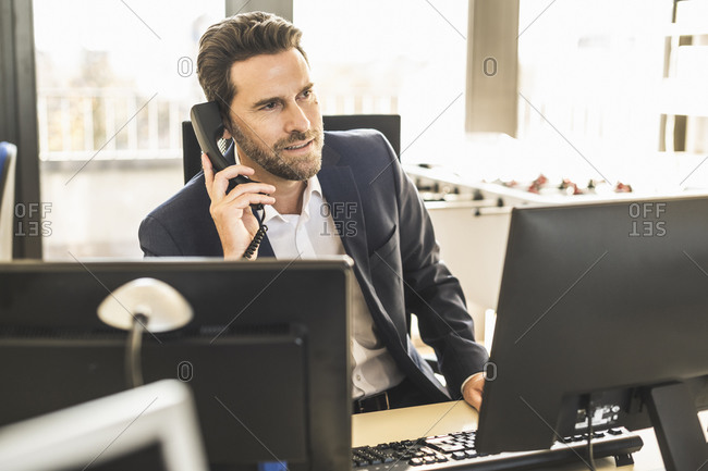 Mature businessman talking on telephone while sitting at office