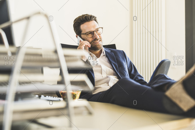 Smiling businessman talking on mobile phone while sitting at office