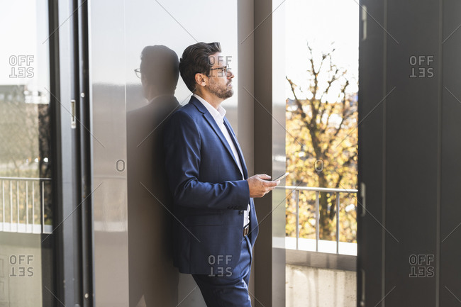 Businessman using mobile phone while standing by balcony at office