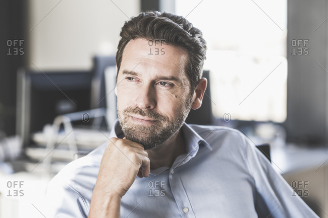 Thoughtful businessman with hand on chin looking away while sitting on chair at office