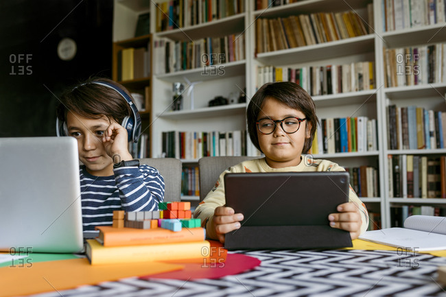 Smiling boy e-learning through laptop while male friend peeking at home