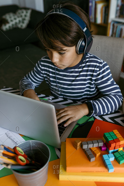 Pre-adolescent boy using laptop during homeschooling