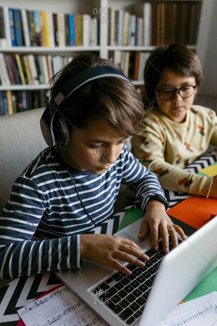 Boy using laptop while e-Learning sitting with male friend at home