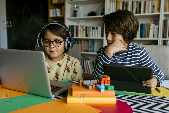 Pre-adolescent boy looking at laptop while e-learning with male friend