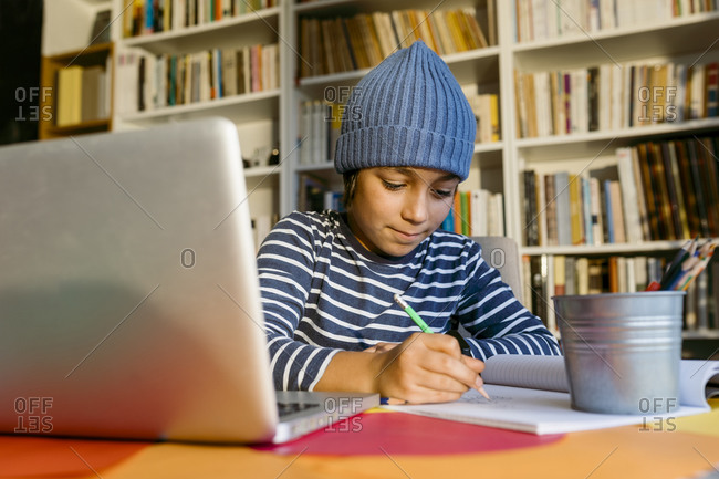 Smiling boy wearing knit hat writing in book while sitting at home