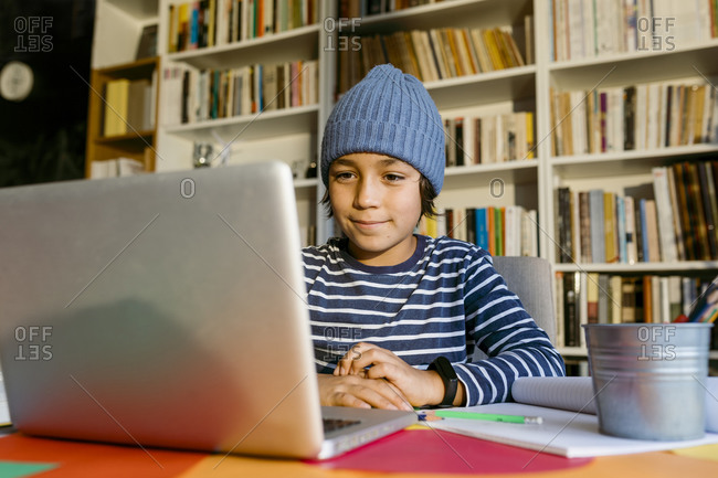 Boy attending homeschooling class through laptop at table in living room