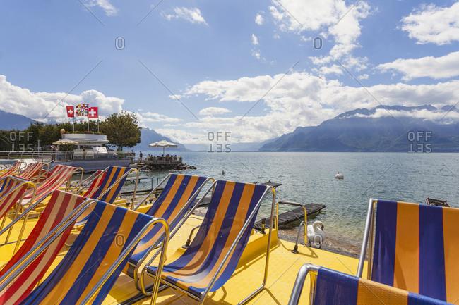 Switzerland- Canton of Vaud- Vevey- Empty deckchairs on shore of Lake Geneva