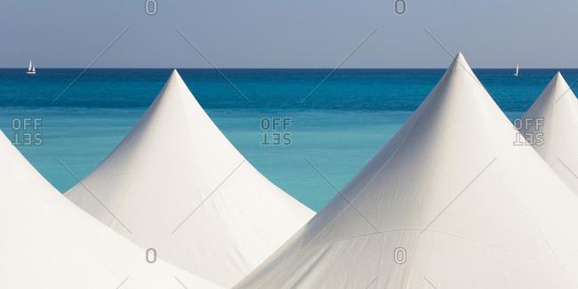 White beach tents against blue coastal water of Mediterranean Sea