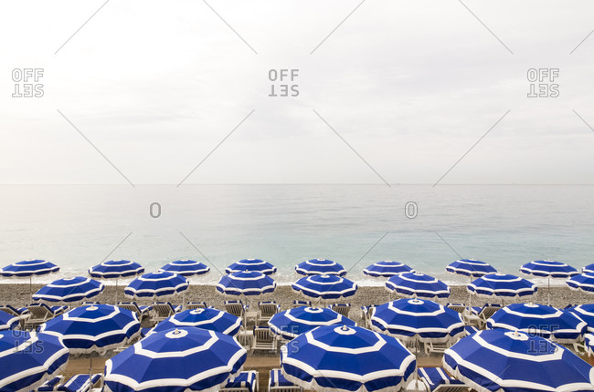 Empty deck chairs and beach umbrellas along coastal beach of French Riviera