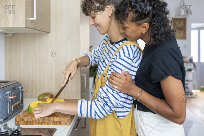 Smiling lesbian couple cutting mango fruit while standing in kitchen at home