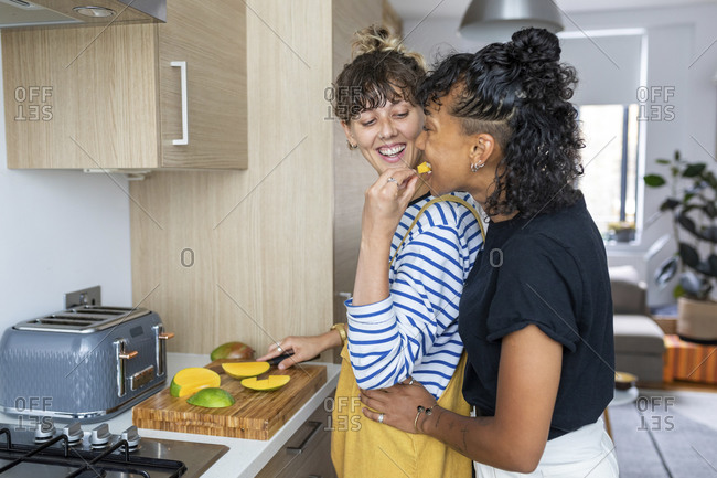 Smiling woman feeding fruit to girlfriend while standing in kitchen at home