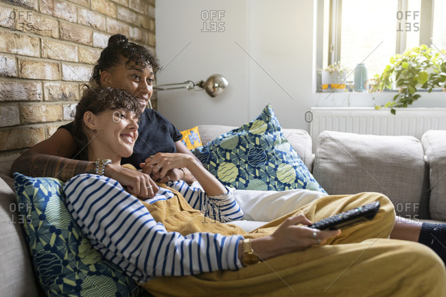 Lesbian couple smiling while watching tv sitting on sofa at home