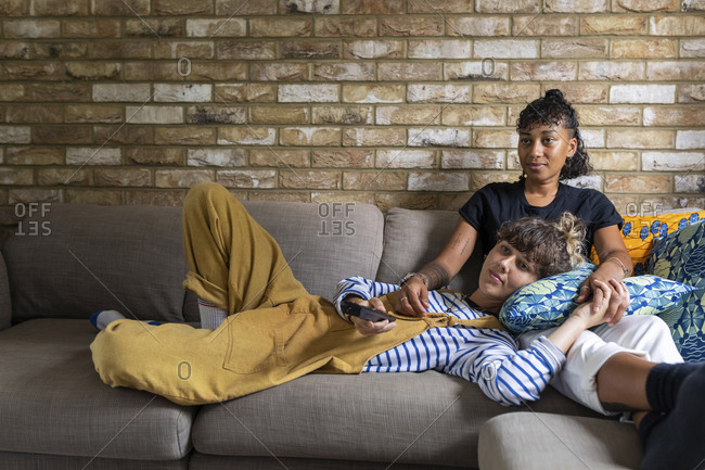 Girlfriend lying on woman's lap while watching tv at home