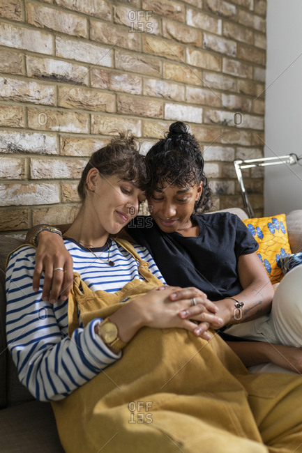 Lesbian couple sitting with hands clasped on stomach while sitting at home