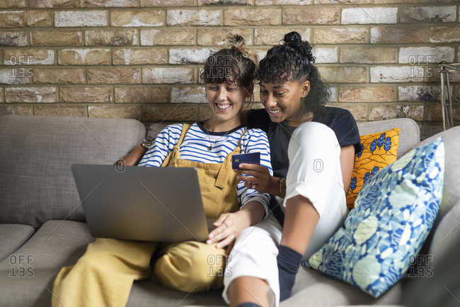 Smiling lesbian couple doing online shopping while sitting at home