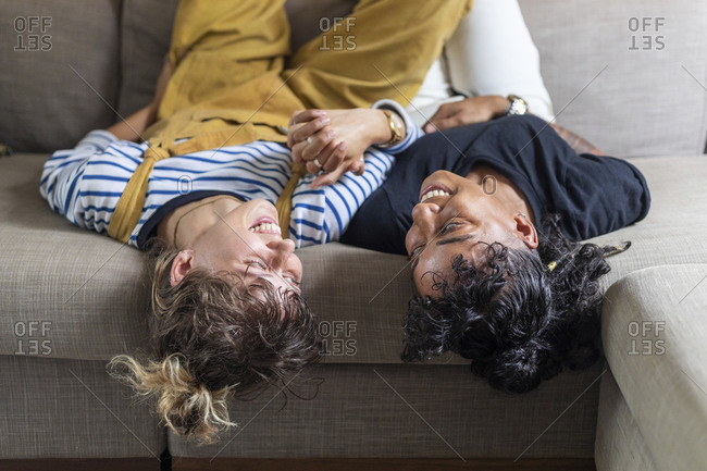 Lesbian couple holding hands while lying on sofa at home