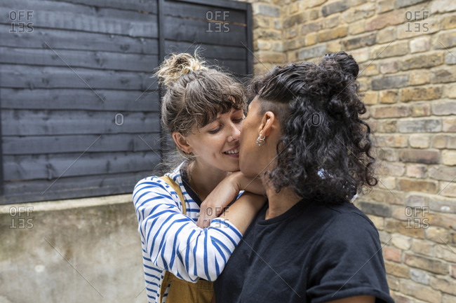 Lesbian couple kissing while standing at back yard