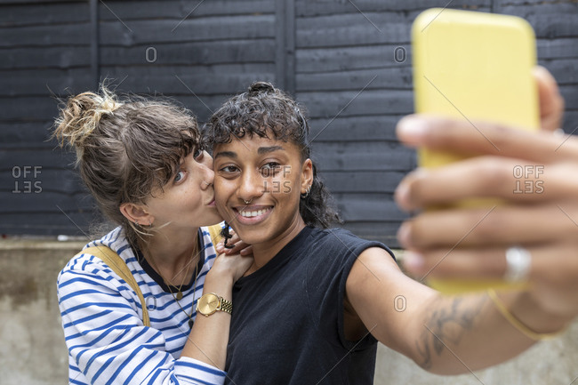 Smiling woman taking selfie on mobile phone while girlfriend kissing her standing at back yard
