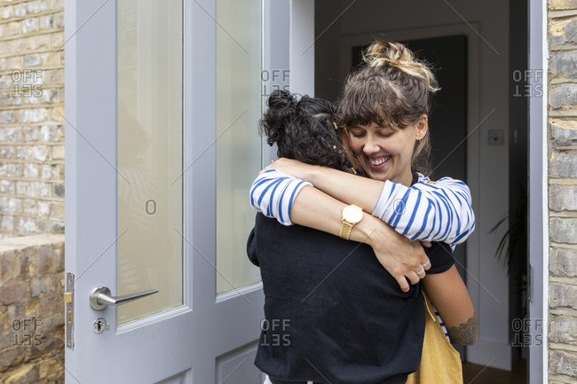 Smiling woman embracing girlfriend while standing at home entrance door