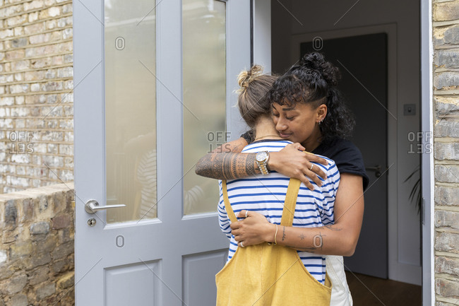 Lesbian couple embracing each other while standing at home entrance door