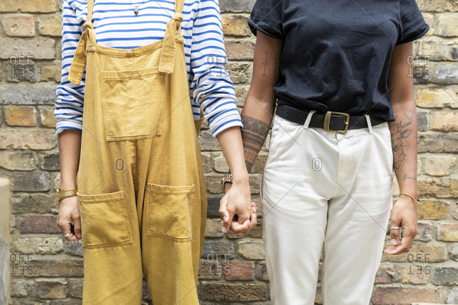 Young lesbian couple holding hands while standing against brick wall