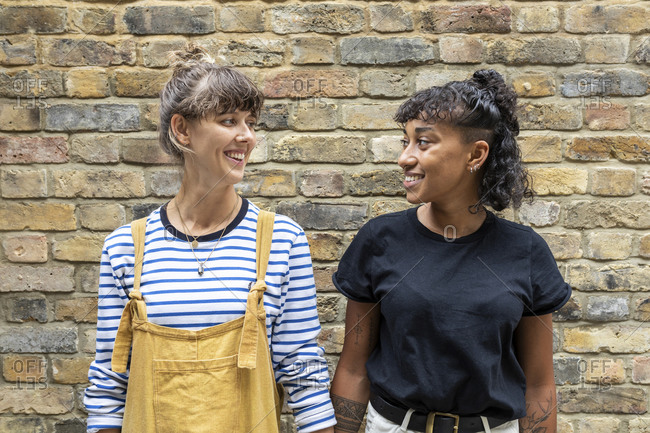 Smiling lesbian couple looking at each other while standing against brick wall