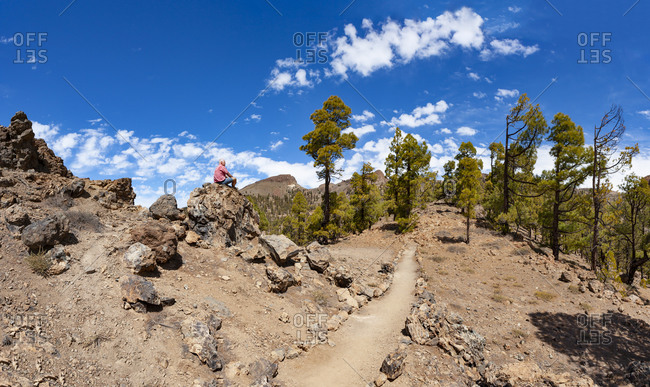 Man sitting on rock while hiking in Teide National Park- Tenerife- Canary Islands- Spain