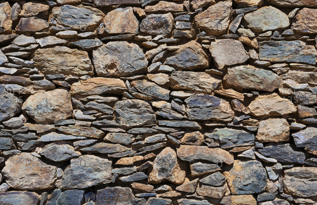 Full frame shot of stone wall on sunny day