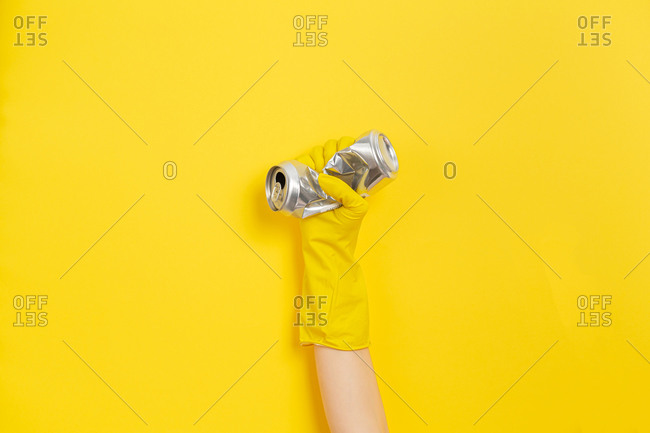 Hand clutches a crushed can as a symbol of the struggle for nature. Yellow background