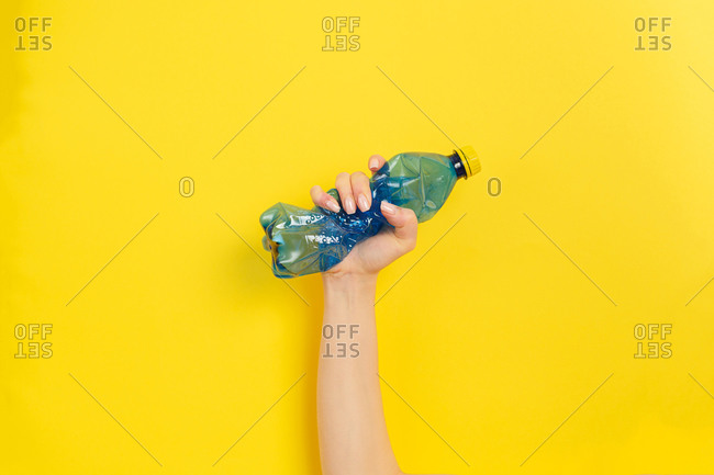 Hand in rubber glove clutches a plastic bottle as a symbol of the struggle for nature. Yellow background