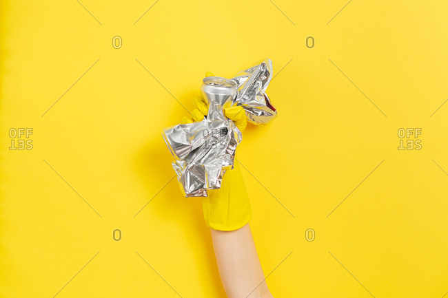 Hand in protective glove clutches garbage as a symbol of the struggle for nature. Yellow background