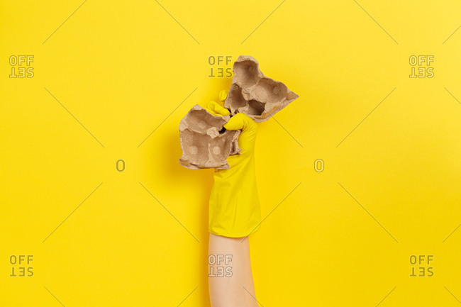 Hand in protective glove clutches carton as a symbol of the struggle for nature. Yellow background