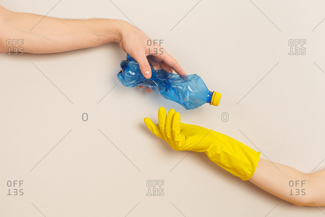 Woman's hand gives plastic bottle to a hand wearing a protective glove on a gray background