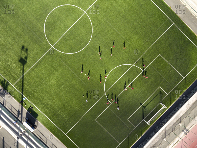 Bird's eye view of kids practicing before a soccer game in the stadium